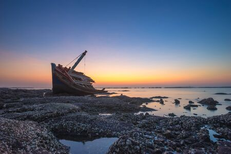 Fishing boat aground on the rocks for a long time at sea erosion disintegrated until only half a body which remains beautiful during twilight.