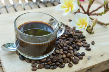 Cup of coffee with coffee beans on a beautiful flower.