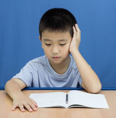 Asian Kid reading book on blue background photo