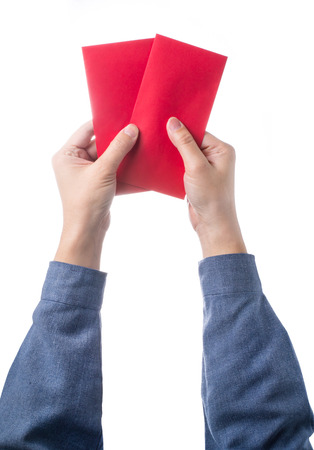 Hand holding chinese red envelope isolated over white background photo