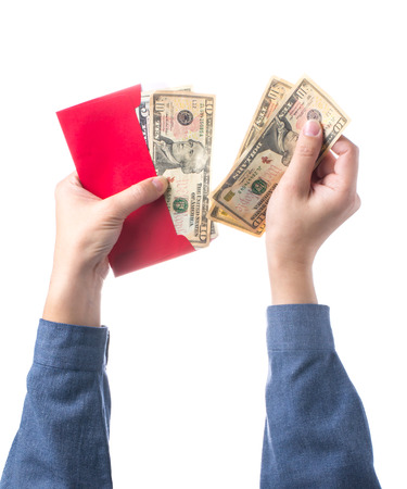 Hand holding chinese red envelope with money isolated over white background photo