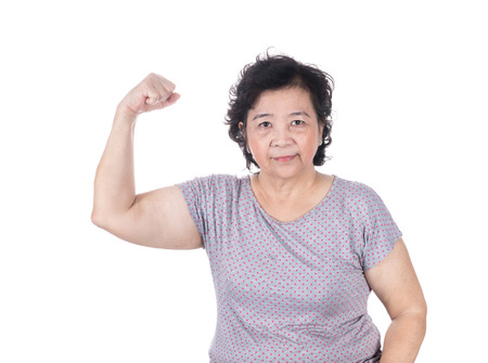 Strong Asian senior female showing off her biceps flexing muscles his arm, isolated on white background.