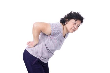 Aziatische oudere vrouw met een zieke rug, rugpijn, geïsoleerd op een witte achtergrond. Stockfoto