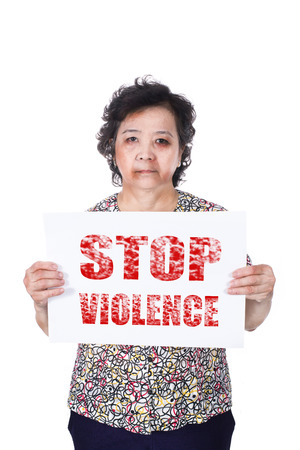 mistreatment: Senior abuse or elder mistreatment with a black eye bruised and injured holding Stop violence horizontal paper. Stock Photo