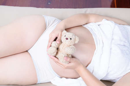 pregnant woman with hands and have bear doll. photo