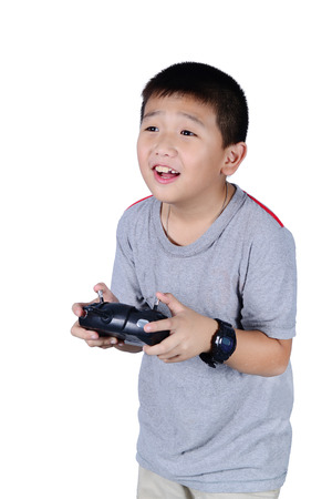 piloting: Little boy holding a radio remote control (controlling handset) for helicopter , drone or plane Isolated on white background. Stock Photo
