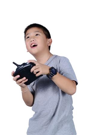 Kleine jongen die een draadloze afstandsbediening (controlerende handset) voor de helikopter, drone of vliegtuig geïsoleerd op een witte achtergrond.