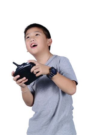 Little boy holding a radio remote control (controlling handset) for helicopter , drone or plane Isolated on white background. Archivio Fotografico