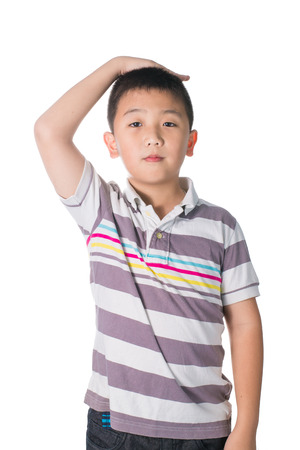 children hands: Boy growing tall and measuring himself, isolated on white background. Stock Photo