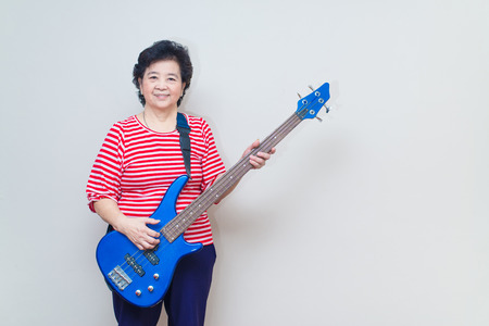 bass guitar women: Portrait of adult asian woman smiling and play electric bass, specialty toned, studio shot with soft shadow, good healthy