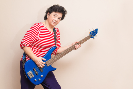 bass guitar women: Portrait of adult asian woman smiling and play electric bass on reddish yellow gray wall background with soft shadow, warm tone Stock Photo