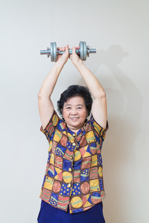 woman shadow: Strong Asian senior woman lifting weights, in studio shot, specialty tones with soft shadow