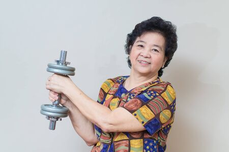 exertion: Strong Asian senior woman lifting weights, in studio shot, specialty tones with soft shadow