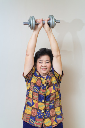 fortitude: Strong Asian senior woman lifting weights, in studio shot, specialty tones with soft shadow