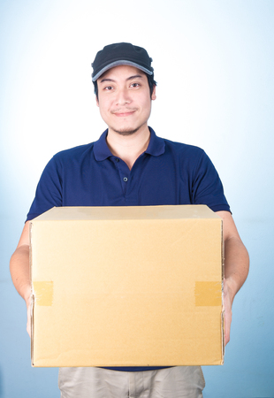 box: Smiling handsome asian delivery man wearing cap, giving and carrying parcel, cardboard box, give thumbs up, on blue background