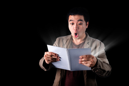 way out: Asian businessman open book with light coming from pages on dark background, found the secret, way out,