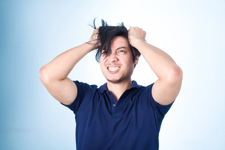 Asian handsome man holding his head frowning with worry screaming. Man pulling his hear for worry, sadness, desperation, so serious, funny, on blue background