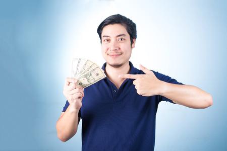 Succesvolle Aziatische man. Gelukkig jonge man die geld terwijl staan ??en duimen omhoog, op een blauwe achtergrond