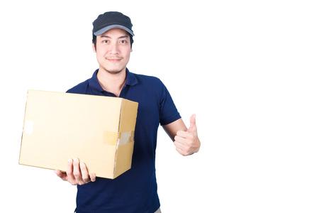 Glimlachende knappe Aziatische levering man met pet, geven en het dragen perceel, kartonnen doos, duimen op te geven, op een witte achtergrond