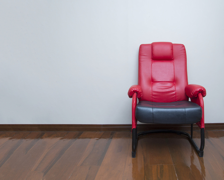 red wall: Modern red and black leather armchair sofa on wood floor interior, room