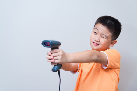 barcode: Asian boy aim a fake gun made with barcode scanner, studio shot, on gray wall background with soft shadow