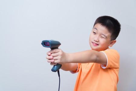codigo de barras: Muchacho asiático apuntar una pistola falsa hecha con un escáner de código de barras, tiro del estudio, en el fondo gris de la pared con la sombra suave Foto de archivo
