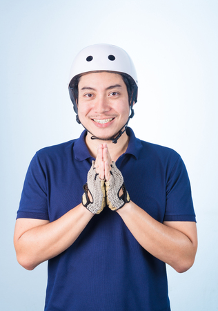 defiant: Asian guy welcome Greeting Sawasdee with bicycle helmet and gloves, on blue background