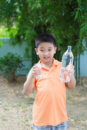 garden green: Asian boy pouring water into glass from bottle, in garden, green background