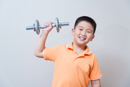 fortitude: Asian strong boy lifting weights, on grey wall background with soft shadow
