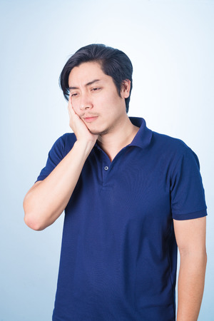 Asian guy having toothache holding his face with his hand, on blue background