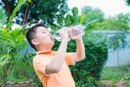garden green: Asian boy drinking water from bottle, in garden, green background Stock Photo