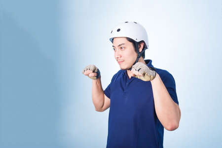 defiant: Asian guy gesture biking bicycle, with bicycle helmet and gloves, on blue background Stock Photo