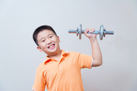 strong boy: Asian strong boy lifting weights, on grey wall background with soft shadow