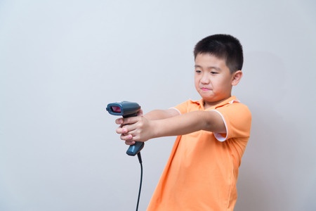 barcode scanner: Asian boy aim a fake gun made with barcode scanner, studio shot, on gray wall background, focus at scenner