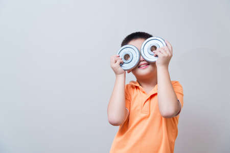 fortitude: Asian boy joking gesture wearing fake glasses made with iron dumbbell, concept idea, on grey wall background with soft shadow Stock Photo