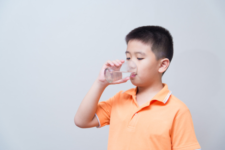 Asian boy drinking water from glass, on grey wall background with soft shadow Imagens