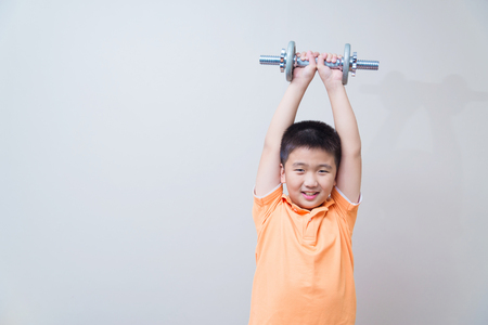exertion: Asian strong boy lifting weights, on grey wall background with soft shadow