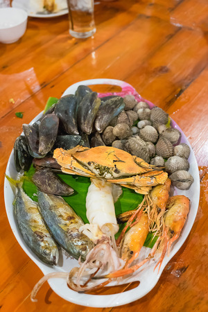 seafood platter: Seafood on white dish, Seafood platter on wood table, shallow DOF