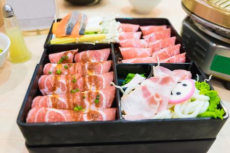 pot belly: Pink kamaboko sliced, japanese fish cake, pork belly sliced and kurobuta pork slices with bacon and udon Noodle on plates, for sukoyaki and yakiniku hot pot shabu, japanese food. ready to served, Shallow DOF