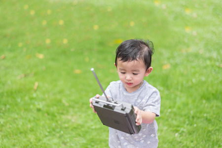 school yard: Little Asian kid holding a radio remote control (controlling handset) for helicopter , drone or plane at the playground, school yard. Happy kid in kindergarten or preschool.
