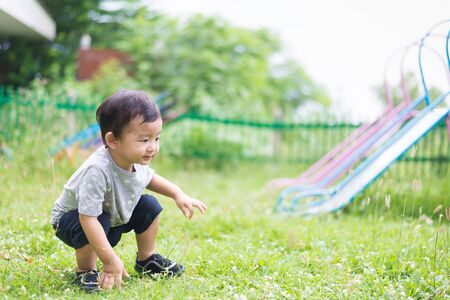 toddler boy: Little Asian kid playing and smiling at the playground under the sunlight in summer, Kids play on school yard. Happy kid in kindergarten or preschool. shallow DOF