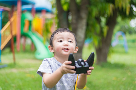 school yard: Little Asian kid holding a radio remote control (controlling handset) for helicopter , drone or plane at the playground, school yard. Happy kid in kindergarten or preschool.shallow DOF