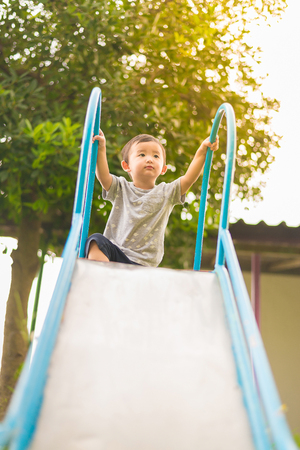 school yard: Little Asian kid playing slide at the playground under the sunlight in summer, Kids play on school yard. Happy kid in kindergarten, color tone, shallow DOF Stock Photo