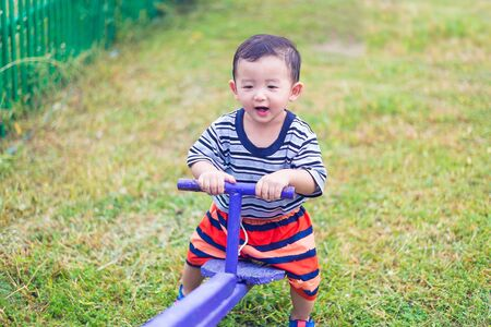 totter: Happy kid play �teeter-totter in kindergarten or preschool, blue color tone, shallow DOF Stock Photo