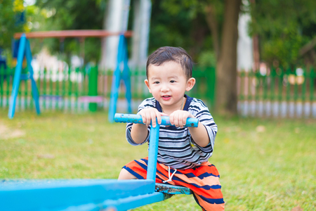 teeter: Happy kid play  teeter-totter in kindergarten or preschool. shallow DOF