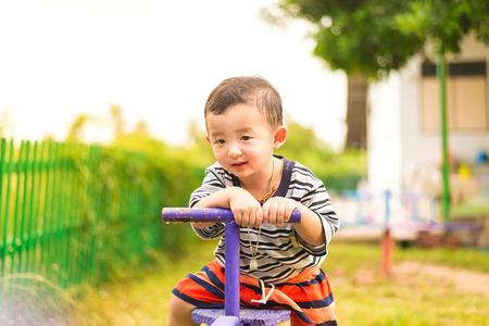Happy kid play �teeter-totter in kindergarten or preschool, color tone. shallow DOF