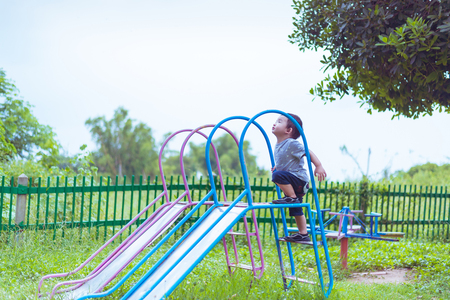 school yard: Little Asian kid playing slide at the playground under the sunlight in summer, Kids play on school yard. shallow DOF and color tone