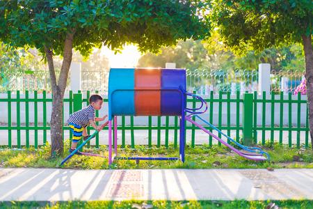 Little Asian kid playing slide at the playground under the sunlight in summer, Kids play on school yard. Happy kid in kindergarten or preschool. shallow DOF