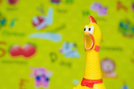 Toy rubber kreet gele kip op onscherpte speelgoed achtergrond in de rommelige kamer, kind ruimte, shellow DOF