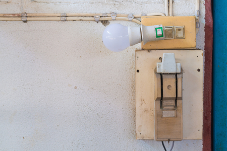 socket outlet: Old electrical power safety breaker and led light with socket outlet on the wall